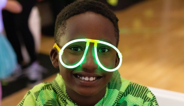 young boy wearing green glow in dark glasses
