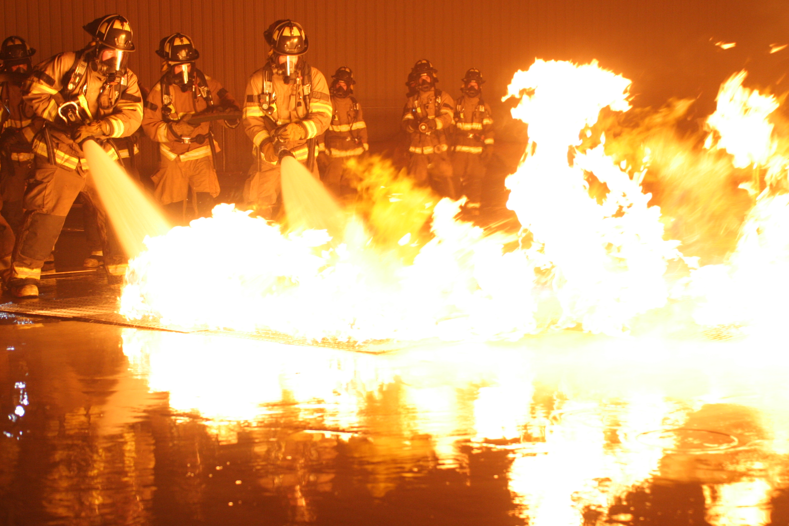 Firefighters engaged in a night training burn.