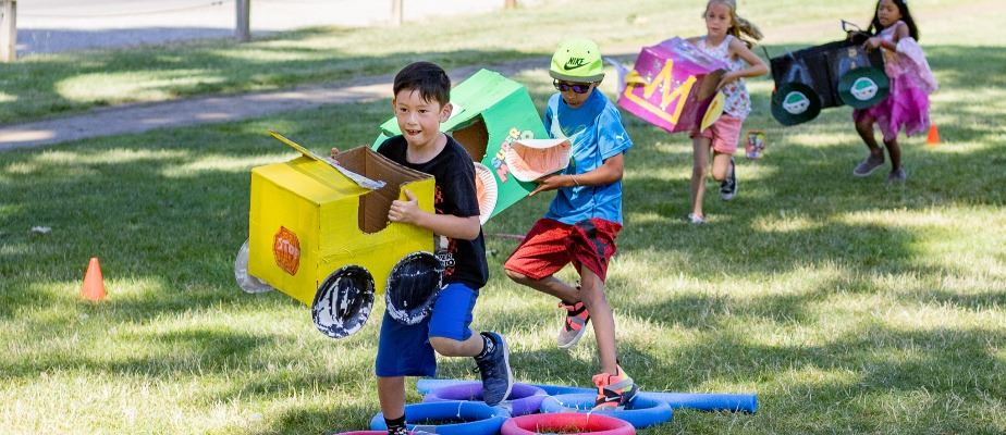Children run an obstacle course with props