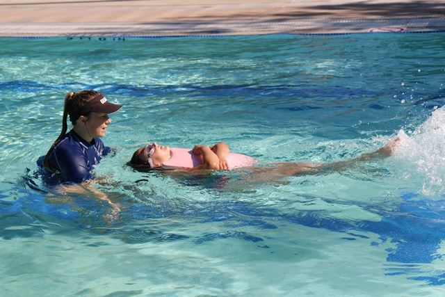 A swimming instructor teaches a student how to float on her back in the pool.