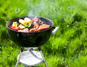 An appetizing assortment of veggies and meat sizzle on a charcoal grill.