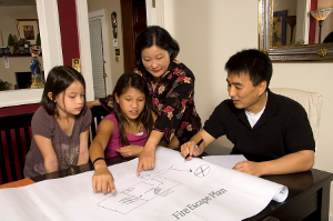 A family looks at a table-sized layout of their home and plans their Fire Escape Plan.