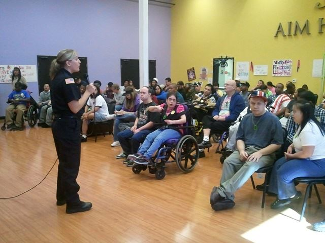 A fire department employee addresses a room full of people at a community presentation.