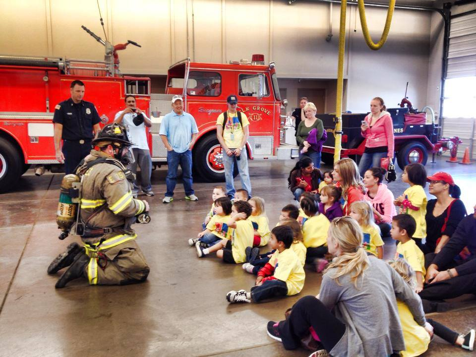 Children sit on the floor and listen as a fire fighter in full gear gives a demonstration