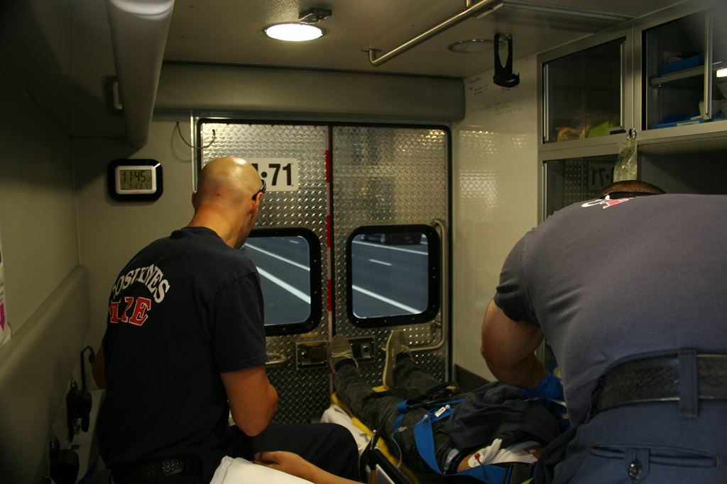 The view inside an ambulance as EMS workers help someone.