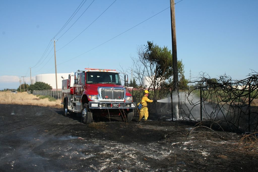 A fire fighter sprays a hose at a grass fire.