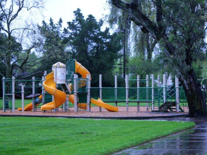 Play equipment with large twisting orange slides