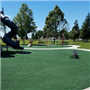 Bright green turf play surface with play equipment and swings