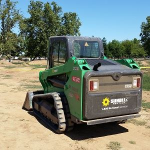 Green and black bobcat used to move dirt and rebuild jumps