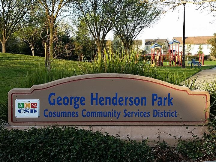 Henderson park sign with green grass and trees