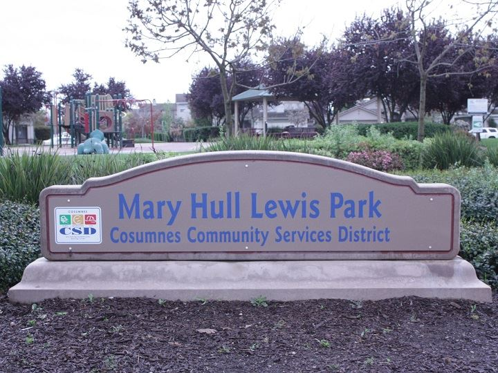 Mary Hull Lewis Park sign, with green landscape and park in the background