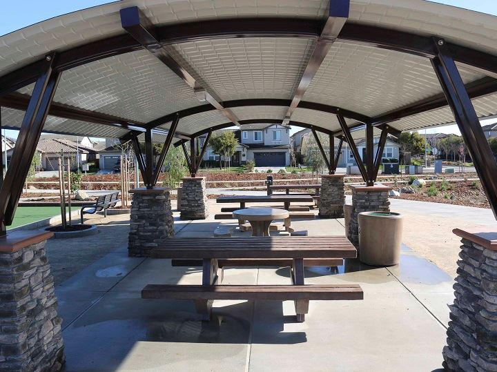 Arching picnic cover in white with brown beams and cement picnic tables underneath