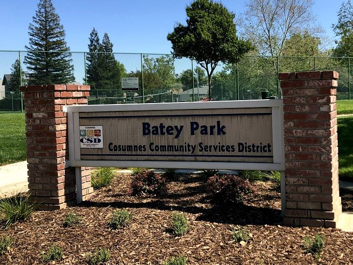 Park sign with tennis courts in the background