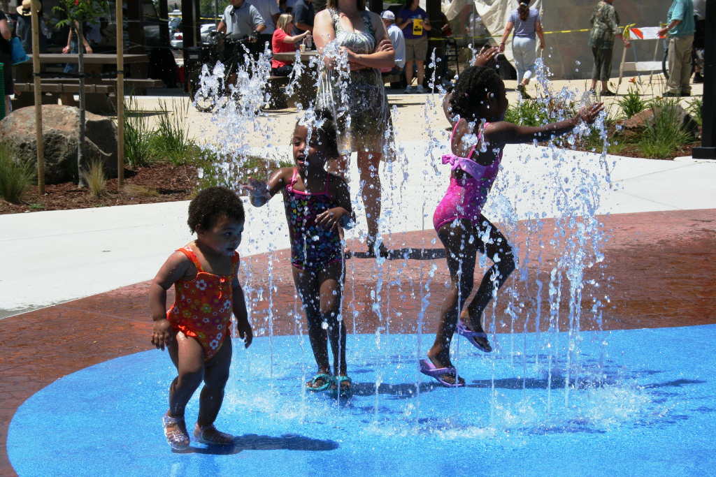 Kids laugh and splash in the Derr Okomoto Park Splash Pad